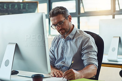 Buy stock photo Shot of a mature designer working on a computer in an office