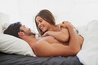 Buy stock photo Shot of a happy young couple relaxing together in bed