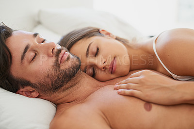 Buy stock photo Shot of a young couple sleeping comfortably in bed