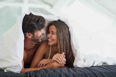Buy stock photo Shot of a happy young couple laying under a duvet together in bed