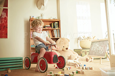 Buy stock photo Shot of a little boy playing on a toy car at home