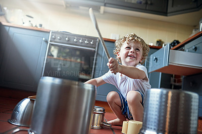 Buy stock photo Shot of an adorable little boy playing drums on a set of pots in the kitchen