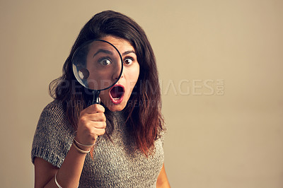 Buy stock photo Studio portrait of a young woman looking shocked while using a magnifying glass against a brown background