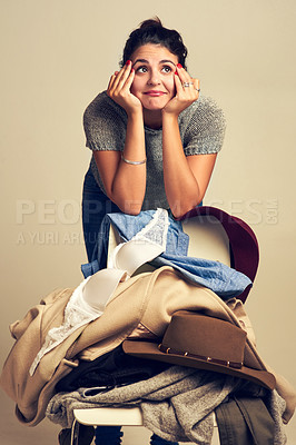 Buy stock photo Studio shot of a thoughtful young woman choosing clothing piled on a chair against a brown background