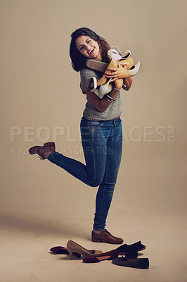 Buy stock photo Studio shot of a joyful young woman holding a lot of shoes against a brown background
