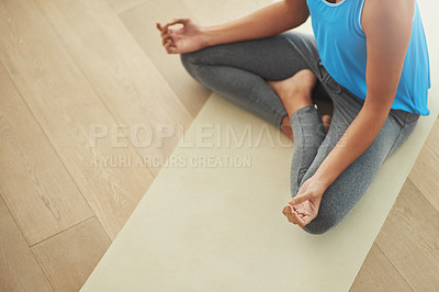 Buy stock photo Cropped shot of a young woman practicing yoga at home