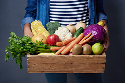 Buy stock photo Studio shot of an unrecognizable woman holding a wooden crate full of fruit and vegetables against a blue background