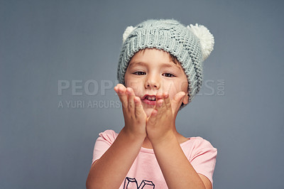 Buy stock photo Studio portrait of an adorable little boy blowing kisses against a gray background