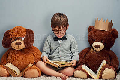 Buy stock photo Studio shot of a smart little boy reading a book next to his teddy bears against a gray background