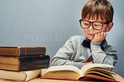 Buy stock photo Studio shot of a smart little boy reading books against a gray background