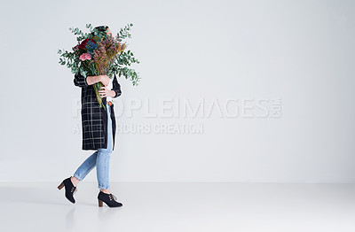 Buy stock photo Studio shot of an unrecognizable woman holding flowers against a grey background