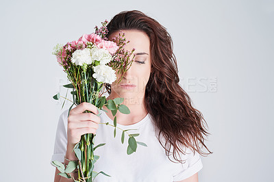 Buy stock photo Studio shot of a beautiful young woman holding a bouquet of flowers against a grey background