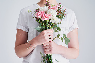 Buy stock photo Studio shot of an unrecognizable woman holding a bouquet of flowers against a grey background