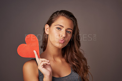 Buy stock photo Studio shot of an attractive young woman holding a blank red heart against a gray background
