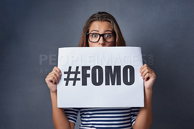 Buy stock photo Studio shot of an attractive young woman holding a sign with #FOMO printed on it against a gray background