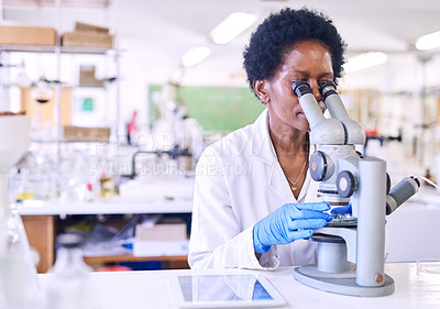 Buy stock photo Shot of a female scientist using a microscope in a lab