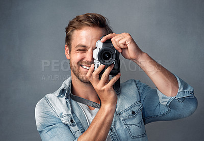 Buy stock photo Portrait of a happy young man holding up a camera while posing against a gray background in the studio