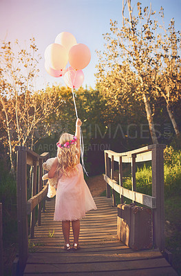 Buy stock photo Shot of a unrecognizable little girl holding balloons and a teddy bear while standing in the middle of a bridge