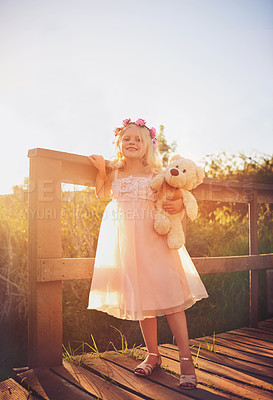 Buy stock photo Shot of a happy little girl holding a teddy bear and looking at the camera while standing on a bridge