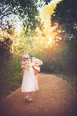 Buy stock photo Shot of a unrecognizable little girl walking with her teddy bear in the middle of a dirt road