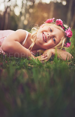 Buy stock photo Shot of a happy little girl looking at the camera while lying on the ground outside in nature