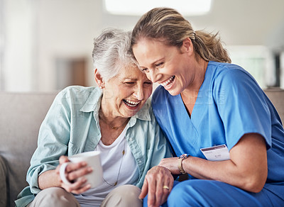 Buy stock photo Shot of a happy young caregiver bonding with her elderly patient on the couch in her home