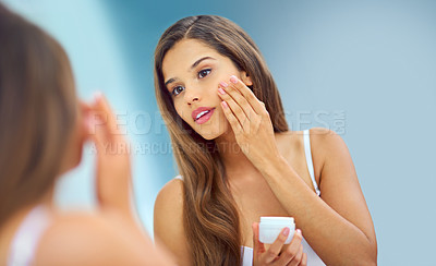 Buy stock photo Shot of an attractive young woman applying moisturizer to her face while looking in the bathroom mirror
