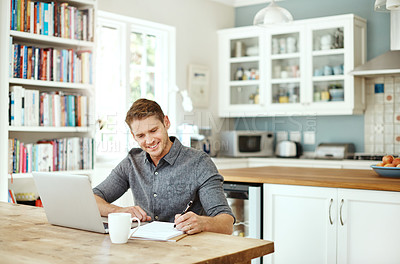 Buy stock photo Shot of a young man using a laptop and writing notes at home