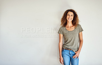 Buy stock photo Shot of a happy and confident young woman standing posing against a gray wall