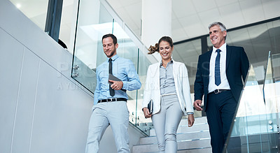 Buy stock photo Shot of a group of colleagues walking down the stairs together in a modern office