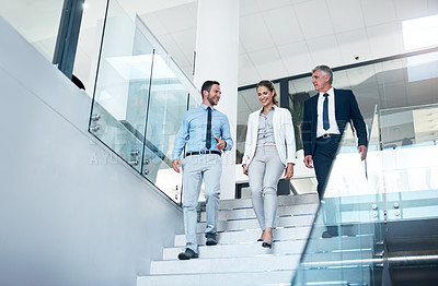 Buy stock photo Shot of a group of colleagues having a discussion while walking in a modern office
