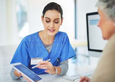 Buy stock photo Shot of a helpful young dietitian showing her senior patient how to fill in a survey on her tablet