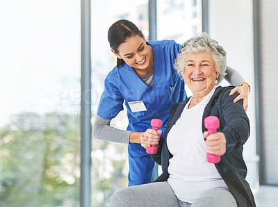 Buy stock photo Shot of a helpful young physiotherapist assisting her elderly patient as she exercises with dumbbells