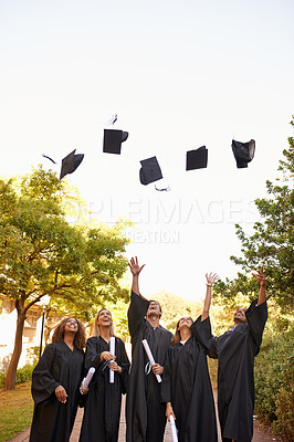 Buy stock photo Cropped shot of a group of university students throwing their hats into the air on graduation day
