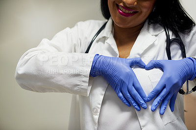 Buy stock photo Shot of an unrecognisable doctor forming a heart shape with her hands against her chest