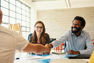 Buy stock photo Shot of creative employees shaking hands in a modern office