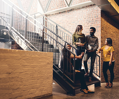 Buy stock photo Full length shot of a group of young designers gathered in a stairwell at the office