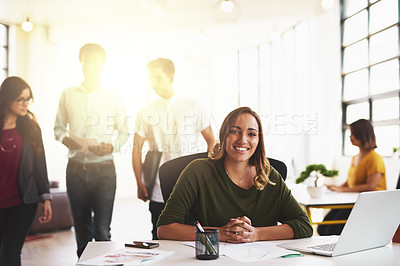 Buy stock photo Cropped portrait of an attractive young woman working in a modern office with her colleagues in the background