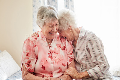 Buy stock photo Shot of two happy elderly women embracing each other at home