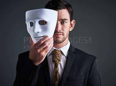 Buy stock photo Studio portrait of a young businessman holding a mask in front of his face against a gray background