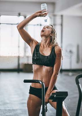 Buy stock photo Shot of a young woman pouring water over her face after a serious workout