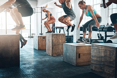 Buy stock photo Shot of a fitness group box jumping at the gym