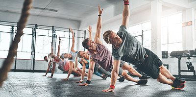 Buy stock photo Shot of a fitness group working out at the gym