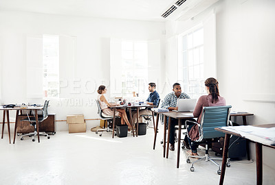 Buy stock photo Shot of a team of young men and women working at their desks in a modern open plan office