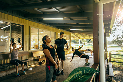 Buy stock photo Shot of a woman working out  with a kettle bell at a training facility
