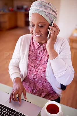 Buy stock photo Cropped shot of a mature muslim woman talking on the phone while sitting by her laptop