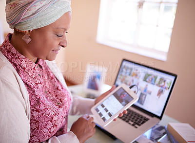 Buy stock photo Cropped shot of a mature muslim woman using her digital tablet while sitting by her laptop