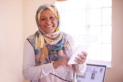 Buy stock photo Cropped shot of a mature muslim woman using her digital tablet at home