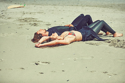 Buy stock photo Shot of a young couple relaxing after a surf at the beach