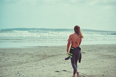 Buy stock photo Shot of a young surfer carrying her surfboard on the beach